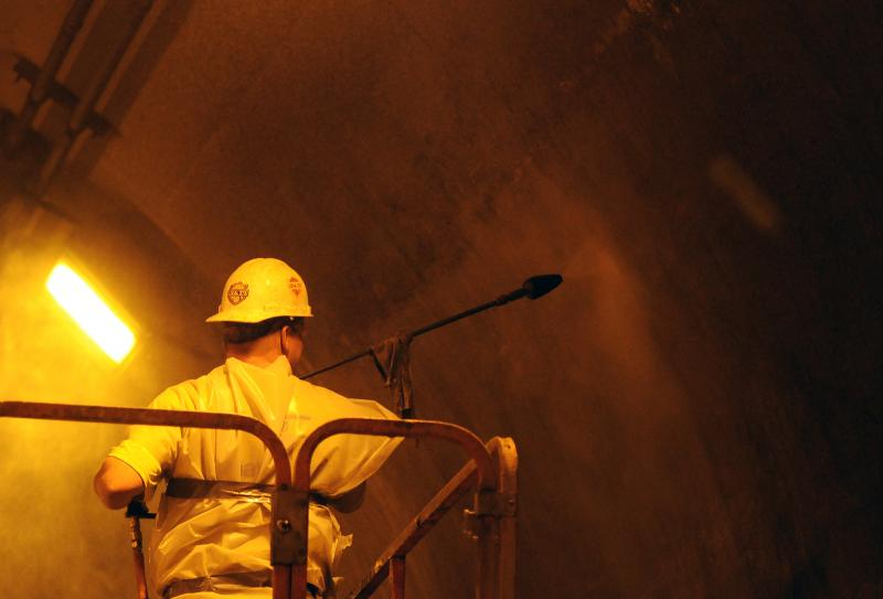 A worker blasts an inbound tunnel wall with water.