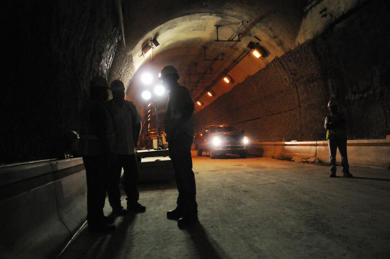 Large, bright lights illuminate a section of the tunnel.