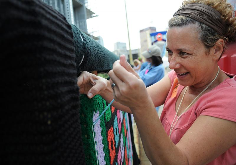 Volunteer Pam Volz, of Mt. Lebanon, attaches a panel to the bridge.