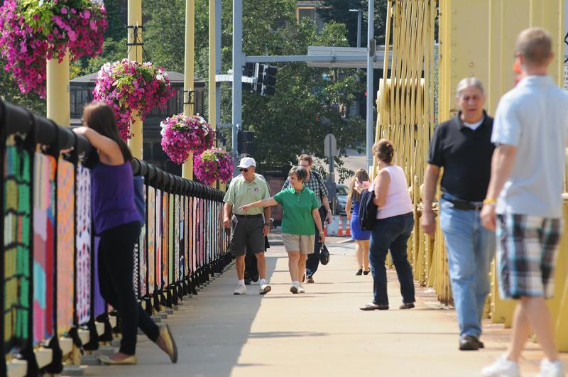 Pedestrians examine the handiwork of scores of artists Monday as the walk along the Andy Warhol Bridge, currently the site of the massive Knit the Bridge yarn bomb project.
