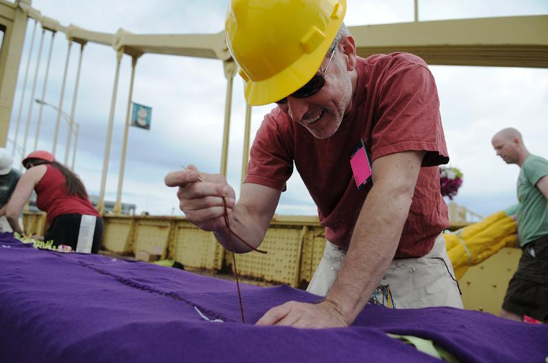 C.T. Steele, a volunteer from Shadyside, sews tower panels before they're installed on Sunday.