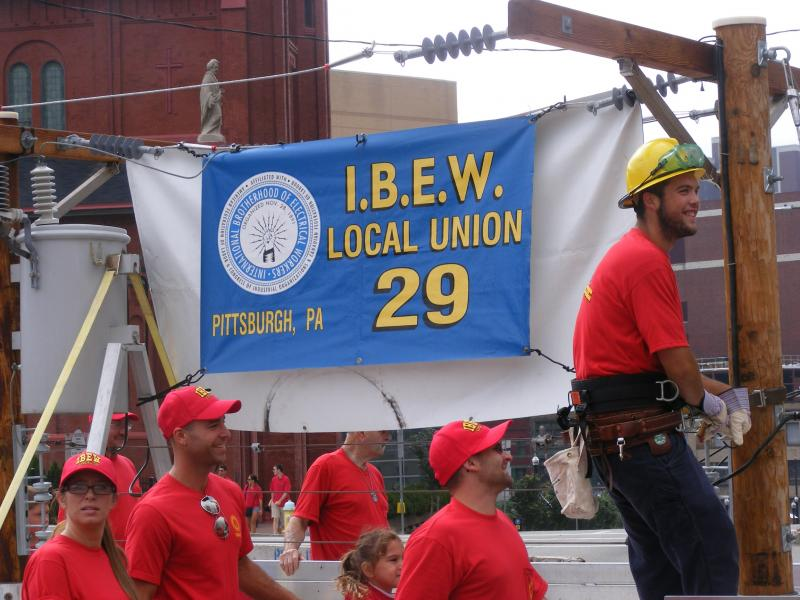 International Brotherhood of Electrical Workers march alongside their float.