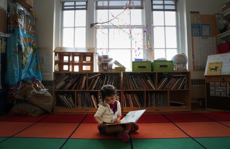 Emma Menta, 4, flips through a book at the Children's School.