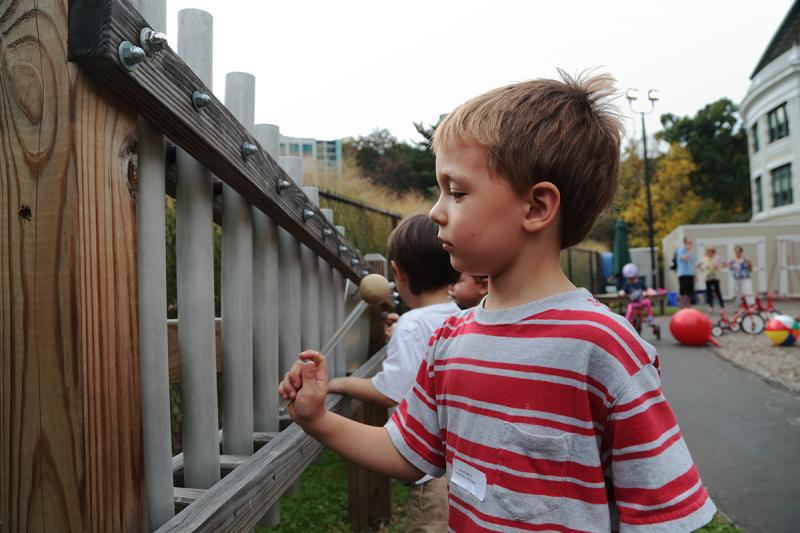 Four-year-old Charlie Wanless plays a large outdoor xylophone while out on the playground area of the Children's School.