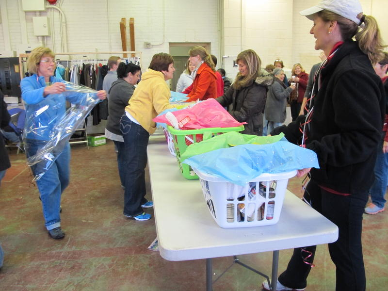 Volunteers pack baskets of Thanksgiving food for needy.