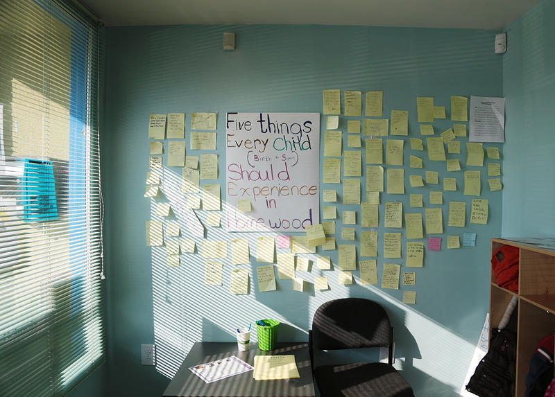 "A wall inside the Homewood Early Learning Hub is lined with Post-it notes listing ""Five things every child (birth to 5 years) should experience in Homewood."""