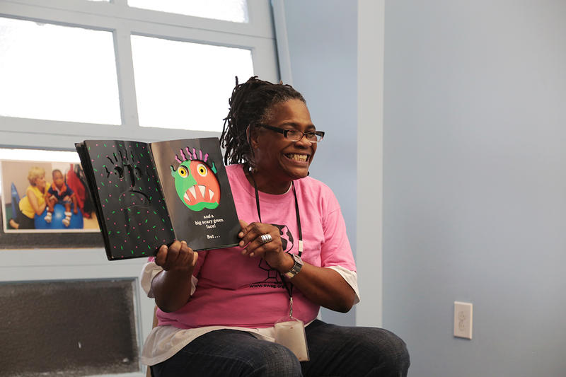 "Cynthia Battle, a community outreach specialist at the Hub, reads the book ""Go Away, Big Green Monster!"" for a group of excited kids on a recent Tuesday play time."