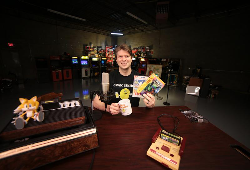 "Mark Bussler poses in his ""Intergalactic Space Arcade,"" where he broadcasts his reviews and answers online fan questions."