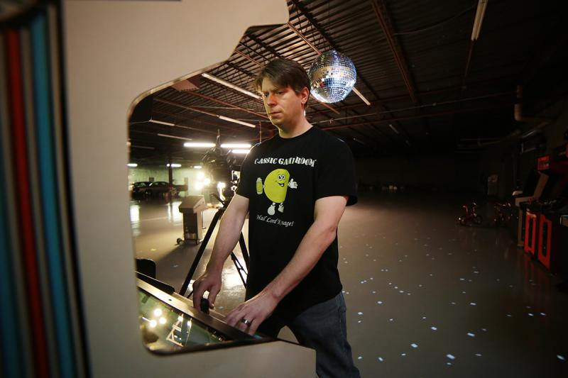 "Bussler plays an arcade game in a large warehouse space — the ""Intergalactic Space Arcade"" — not from his office."