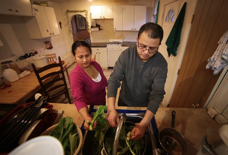 Tek Nepal (right) washes spinach at his Mount Oliver home with his wife Radhika Nepal. After a Type 2 diabetes diagnosis in 2012, his diet has changed substantially.