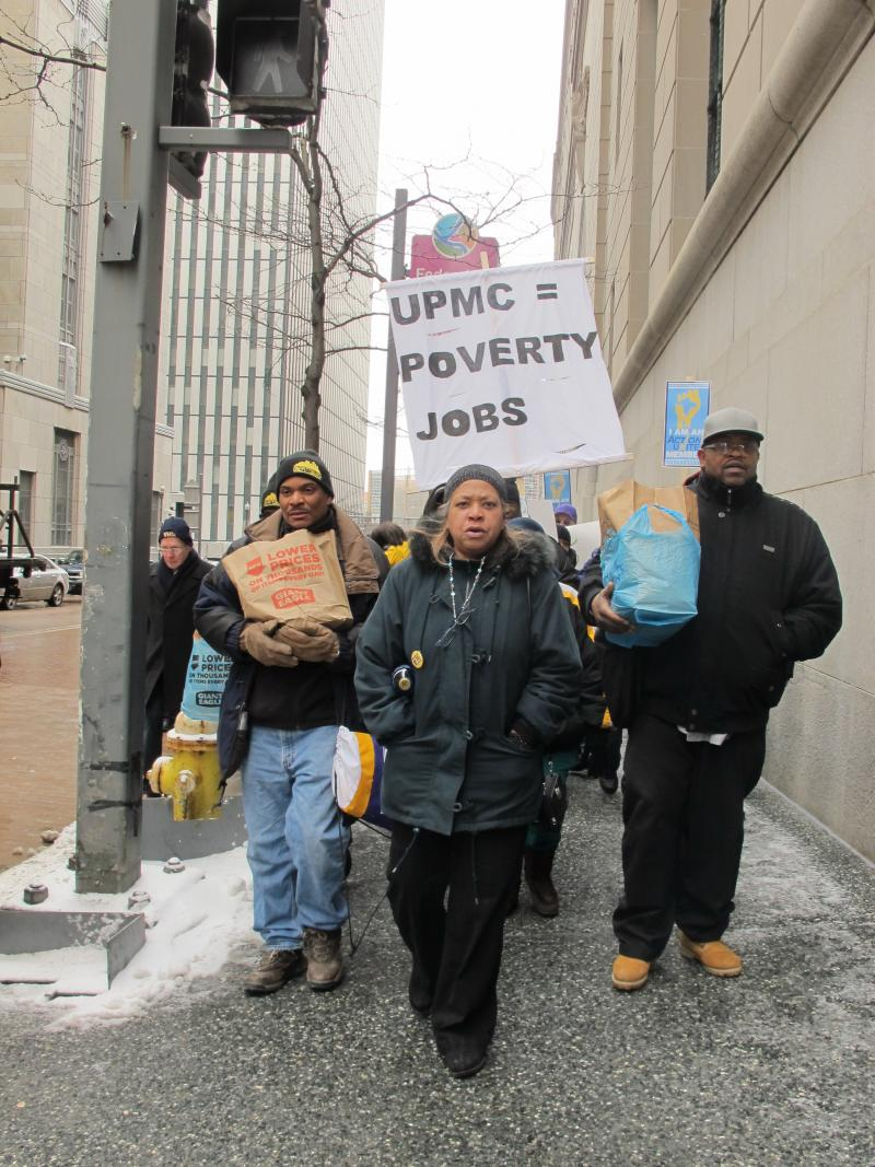 UPMC employee Leslie Poston leads workers on a march to UPMC's headquarters in downtown Pittsburgh.