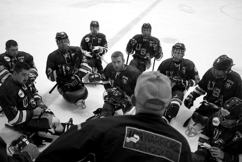 Earl (center) listens to Mike Doyle, coach of the USA Warriors, a sled hockey team whose members have all been wounded in the military.