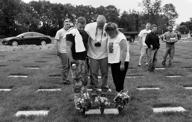 Earl visits the grave of his comrade, Specialist Derek Holland, five years after the roadside bomb took his life. With him are Holland's parents, Kathy Andreas-Heath and Michael Heath.