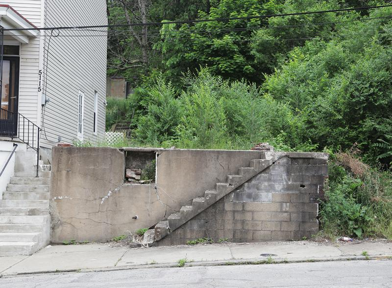 A crumbling staircase leads to a vacant lot on Kincaid Street in Garfield.
