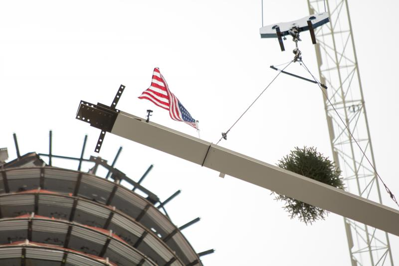 The last beam is hoisted to the top of the building.