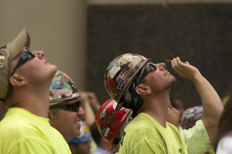 Workers look up at the last beam is raised to the top of the Tower at PNC Plaza.