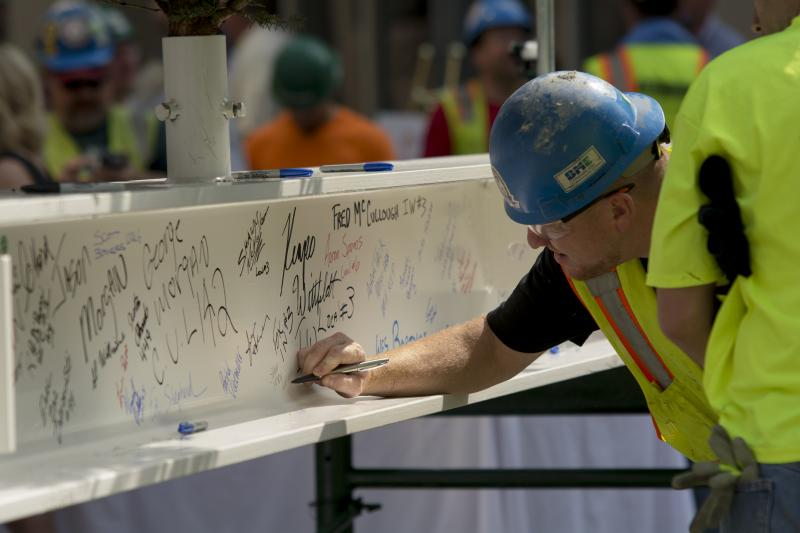 A construction worker signs the last steel beam to be placed atop the Tower at PNC Plaza on Tuesday.