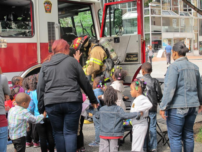 A firefighter shows kids what equipment he wears to respond to an emergency.