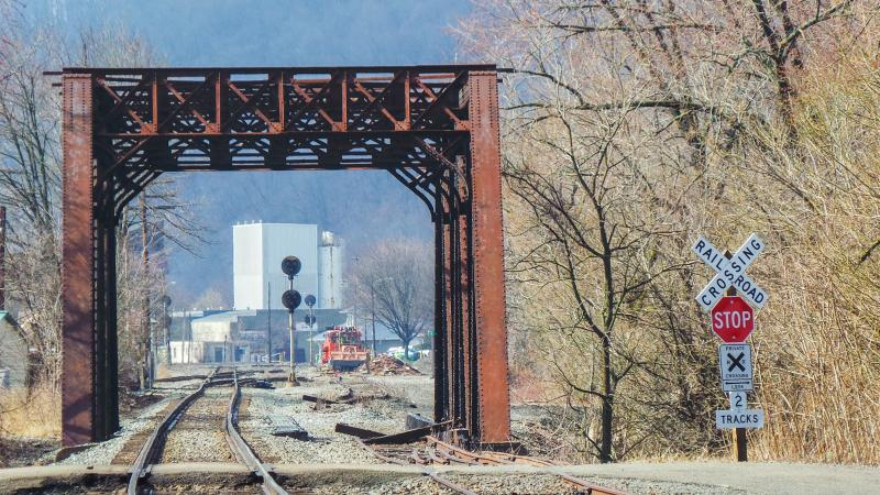 Trains pass frequently along the river side of Monongahela on a daily basis. Many businesses, both open and closed, sit along the rails.