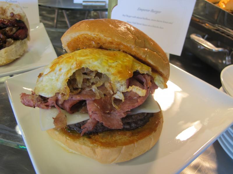 The Emperor Burger features a beef patty with shaved kielbasa, onion bacon kraut, a fried egg and Heinz Field Secret Sauce on a brioche bun.