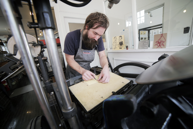 Boan works on a project using a 1929 Chandler & Price platen press.