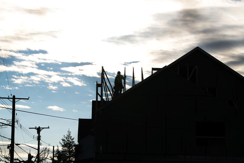 A worker is seen atop a house under construction on Meadow Street in Larimer.