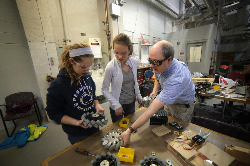 Girls of Steel members Isabella Salvi, 17, (left) and Kyra Halbert-Elliot, 14, work on a robot with team mentor Tom Pope.