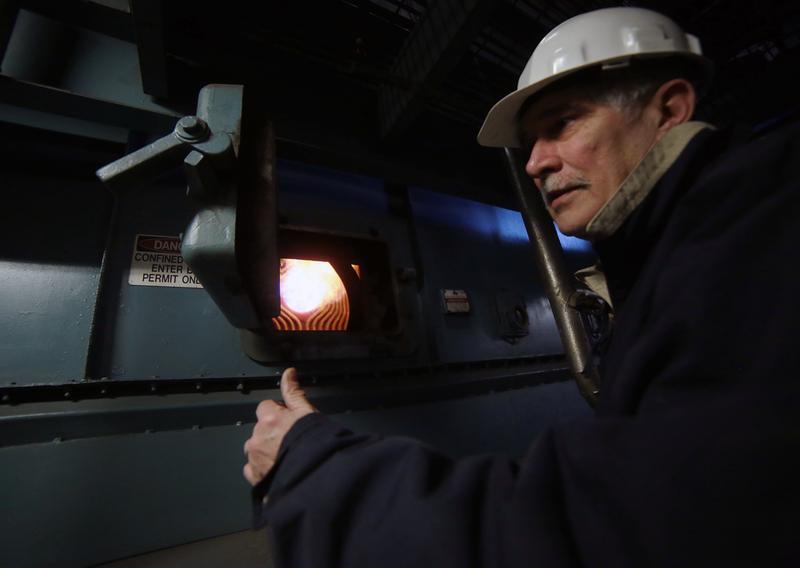 Bellefield Boiler Plant superintendent Bob Miller opens an access door to inspect a boiler's burner.