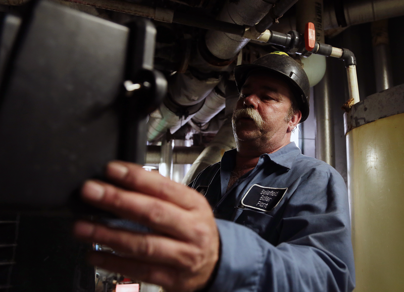 Ron Studer, a repairman at the Bellefield Boiler Plant, regenerates a water softener.