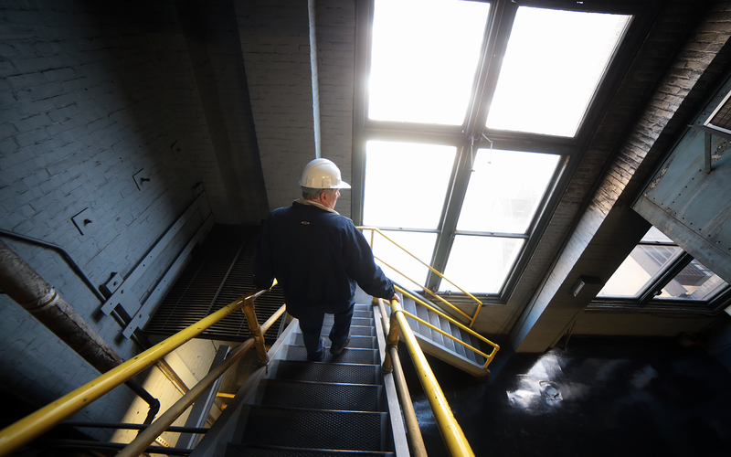 Bob Miller walks down a flight of stairs in the boiler plant.