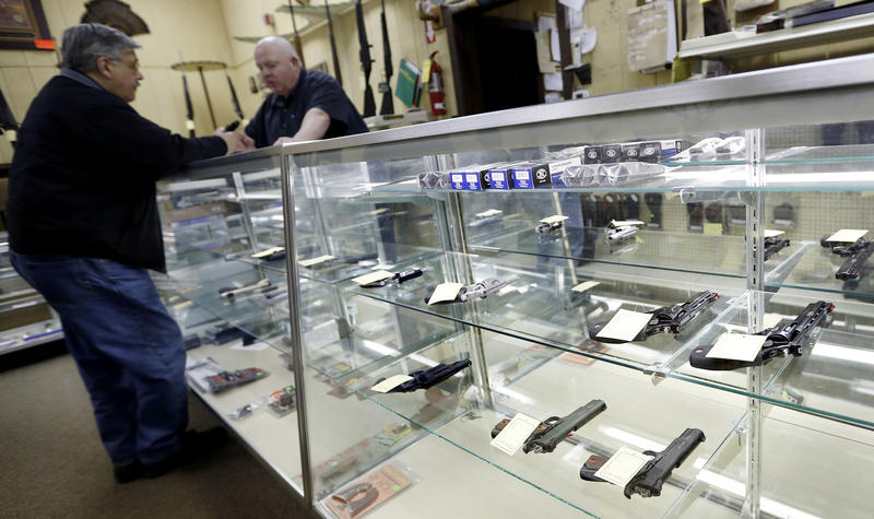 Gun World salesman Alfred Ozga, right, talks with a customer at the sparse display of handguns available at the store on Wednesday, Jan. 16, 2013 in Harrisville, Pa.