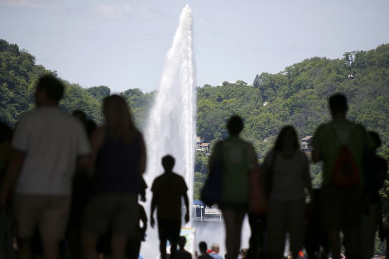 Visitors to the annual Three Rivers Arts Festival are silhouetted against the fountain in Point State Park as they walk under the portal bridge on Saturday, June 7, 2014, in downtown Pittsburgh.