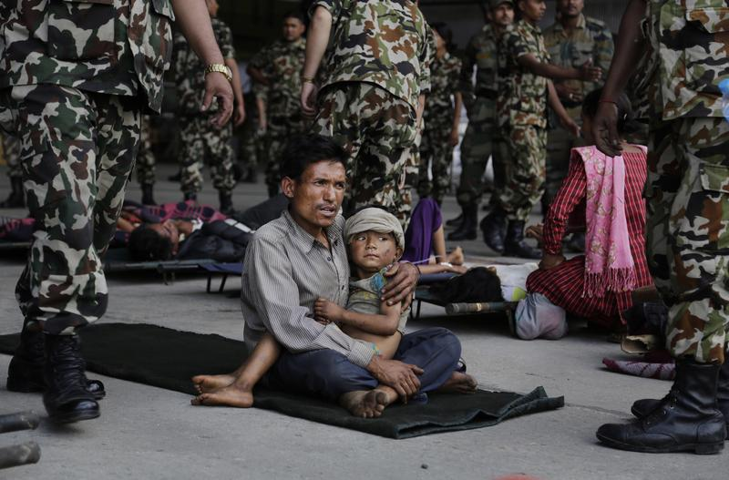 A man sits with a child on his lap as victums of Saturday's earthquake wait for ambulances after being evacuated at the airport in Kathmandu, Nepal, on April 27, 2015.