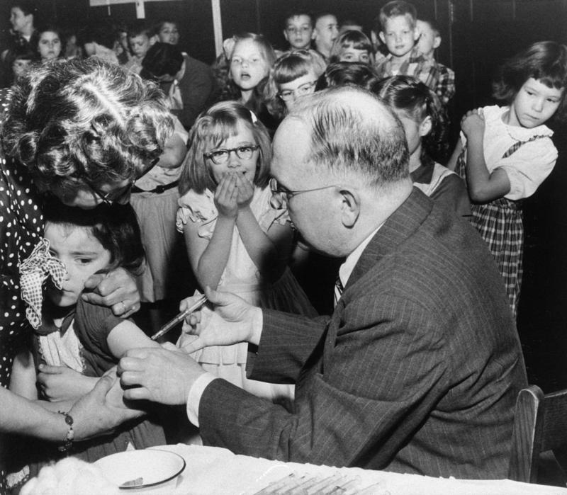 Patsy Murr, first grader at Fulton School in Lancaster, Pa., gets her Salk shot from Dr. Norman E. Snyder as she is held by Mrs. Walter Sourweine, April 25, 1955. Others view the proceedings with mixed emotions.