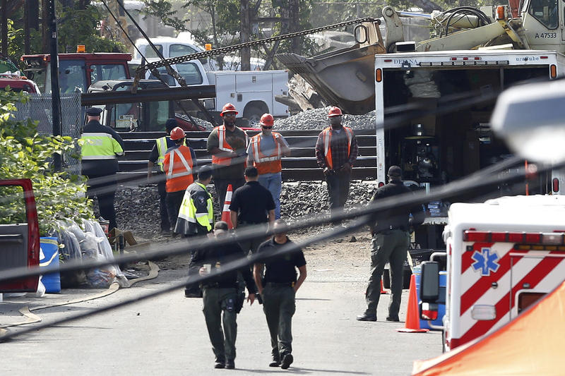 A rail track, top left, is pulled by a front loader as workers labor at the site where a deadly train derailment happened earlier in the week, Friday, May 15, 2015, in Philadelphia.