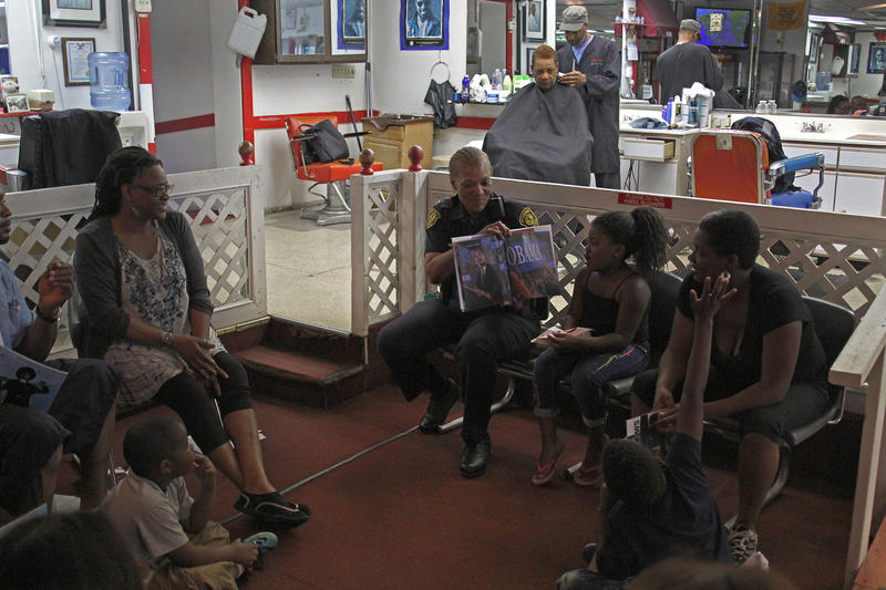 Pittsburgh Police Officer Karen McNeal reads to a group at Willy Tee's barbershop in Homewood as part of the weekly Raising Readers program.