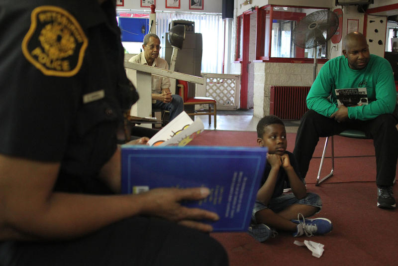 Vergel Clark, 8, waits to listen to a story read by Pittsburgh Police Officer Karen McNeal.