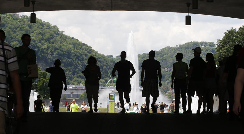 A runner is silhouetted along with visitors to the opening day of the Three Rivers Arts Festival as he runs over the portal bridge past the fountain at Point State Park on Friday, June 5, 2015, in Pittsburgh.