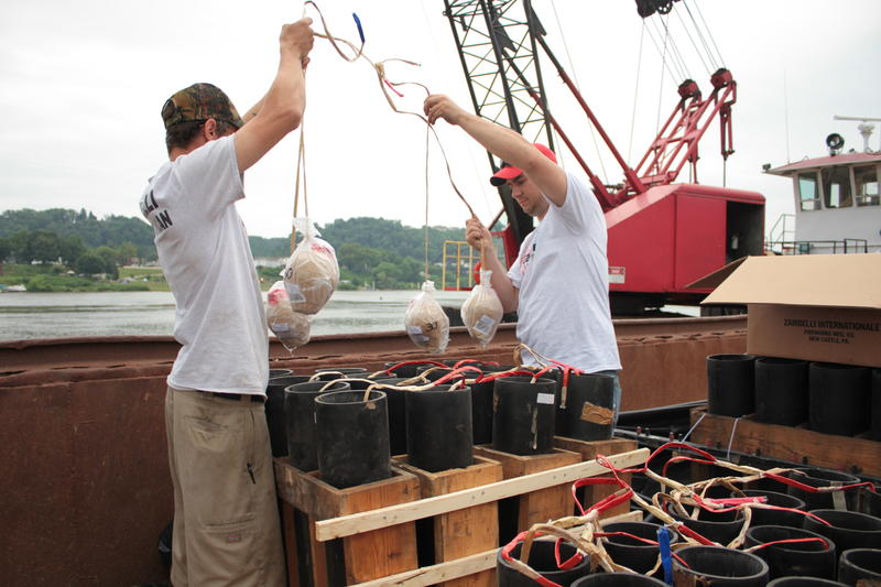 Employees of Zambelli Fireworks Internationale prepare the racks for a fireworks display on a barge in the Ohio River.