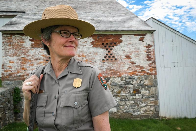 Park ranger Katie Lawhon stands near the Trostle Farm, Gettysburg National Military Park, June 17, 2015. The barn dates back to the time of the battle and is a favorite with tourists because of the cannonball hole left in the brick wall.