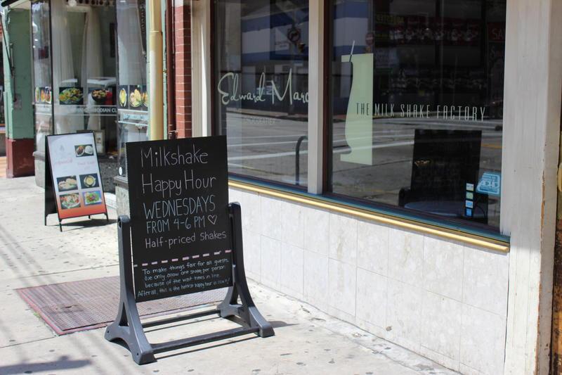 """A sign advertising """"Milkshake Happy Hour"""" outside the Milkshake Factory."""