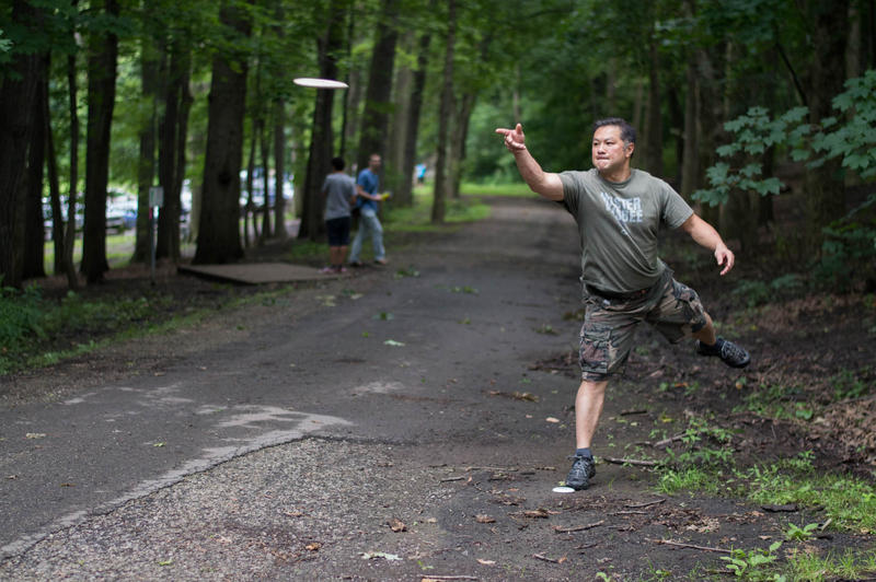 Disc golfer Matthew Miao, of Regent Square, makes a put during a game at Schenley Park on July 8.
