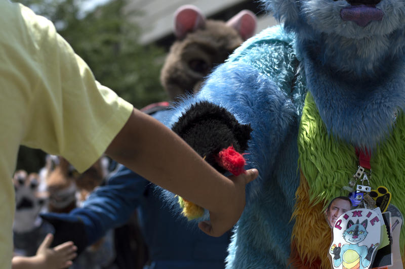 Children and adults reached out for high fives as the furries walked past during the fursuit parade Saturday. Many received hugs from the furries.