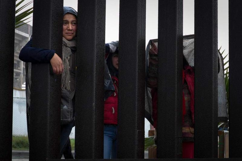 A family stands in the rain on the Mexican side of the border fence as they visit with family at Freedom Park in Border Field State Park in Imperial Beach, California.