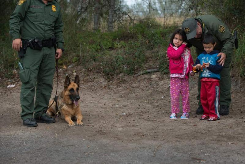 Ruben Garza Jr., a Supervisory Border Patrol Agent, comforts two children as a bus they were traveling on was searched at the checkpoint in Falfurrias, Texas.