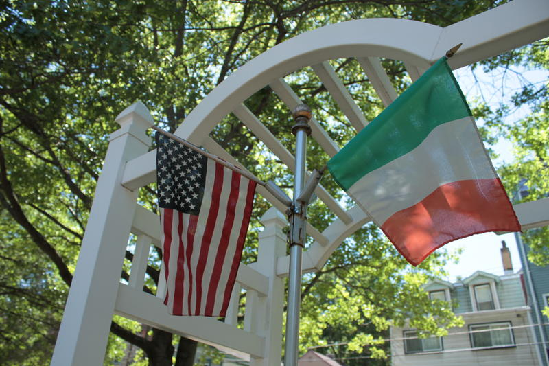 The American and Italian flags fly over a memorial plaque listing 95 family names from Panther Hollow.
