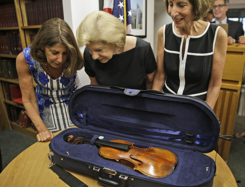 Sisters Amy Totenberg, left, Nina Totenberg, center, and Jill Totenberg get their first look at the Ames Stradivarius violin that was stolen from their father, renowned violinist Roman Totenberg 35 years ago, in New York, Thursday, Aug. 6, 2015.