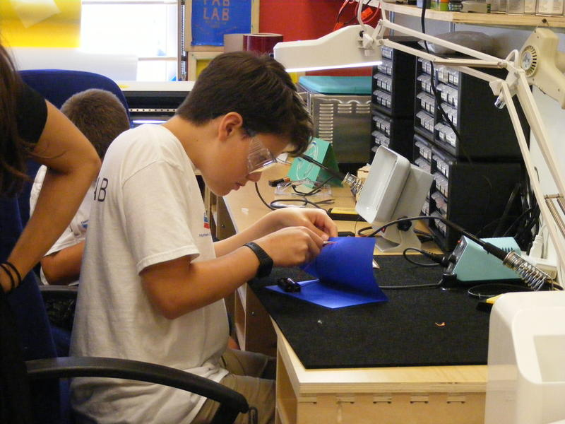 One camper works on attaching LED lights to his project