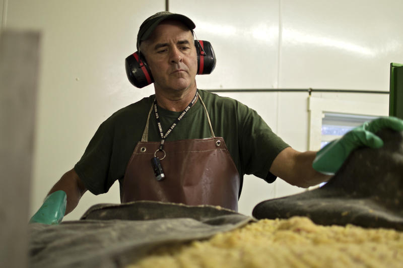 Larry Voll, one of the owners of Soergel's Orchards, prepares apple pulp for pressing.