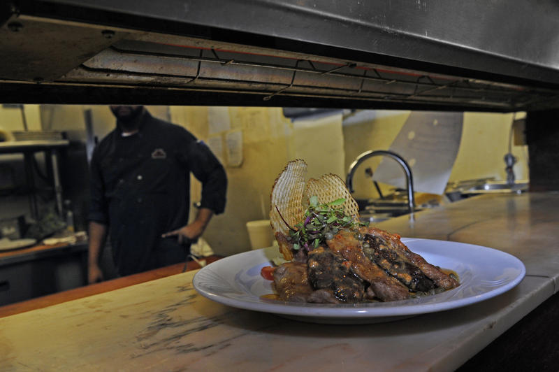 A food service worker at The Carlton Restaurant in Downtown Pittsburgh puts a dish of veal portobello in the window to be served.